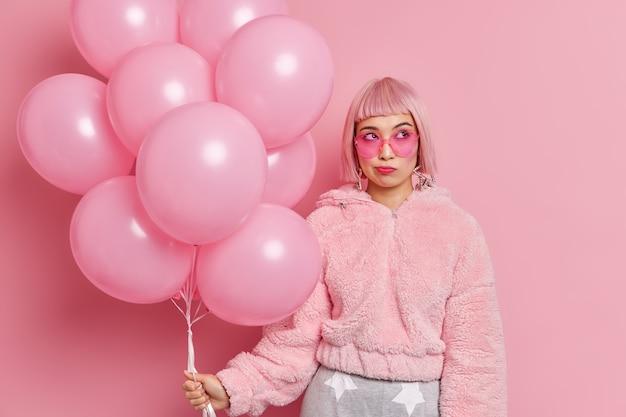 Mulher asiática jovem elegante pensativa tem olhar glamour usa óculos de sol da moda, casaco de pele segura balões inflados, pense que surpresa se preparar para parabenizar o amigo com ocasião especial