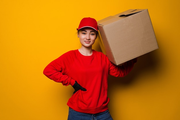 Mulher asiática jovem entregadora segurando e carregando uma caixa de papelão isolada em um amarelo