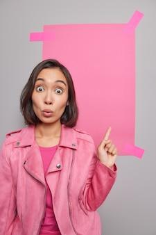 Mulher asiática jovem espantada aponta o dedo indicador para o canto superior direito mostra maquete para anúncios publicitários, sua marca demonstra pôster vazio vestido com jaqueta poses internas.