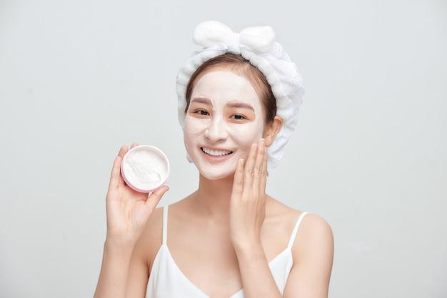 Mulher asiática jovem feliz, aplicando a máscara de argila facial e vestindo uma toalha.