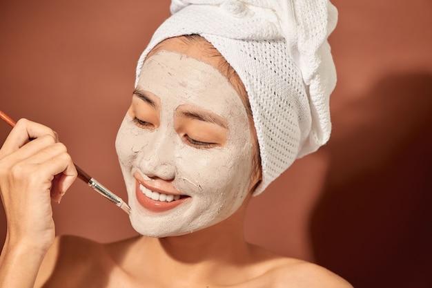 Mulher asiática jovem feliz aplicando máscara de argila no rosto sobre fundo laranja. fechar-se.