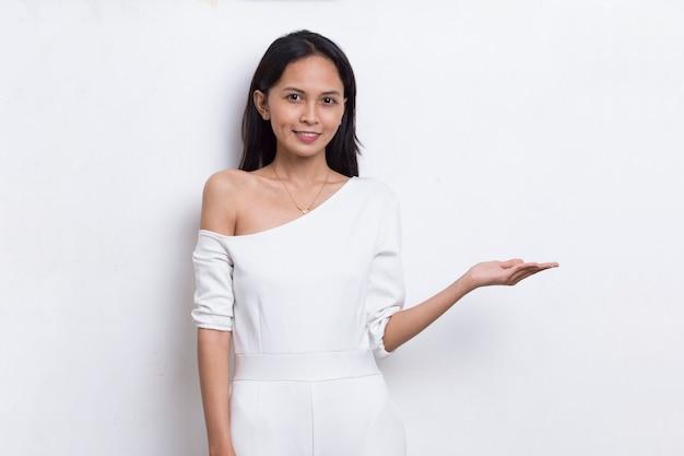 Mulher asiática jovem feliz apontando com os dedos para diferentes direções, isoladas no fundo branco