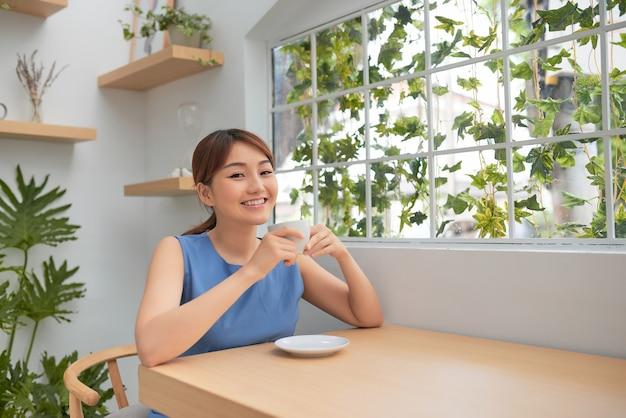 Mulher asiática jovem feliz bebendo café atrás da janela em casa
