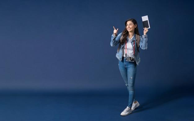 Mulher asiática jovem feliz segurando o passaporte com o cartão de embarque e apontando para o espaço de cópia