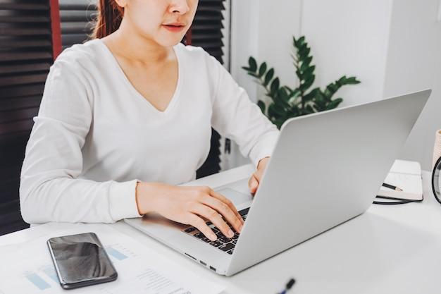 Mulher asiática jovem feliz trabalhar em casa, trabalhando em uma rede social de laptop