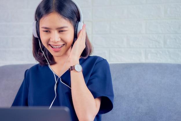 Mulher asiática jovem feliz usando fones de ouvido brancos, ouvindo música de amor e usando o laptop no sofá em casa.