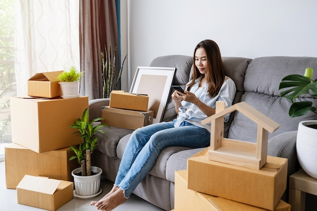Mulher asiática jovem feliz usando smartphone na sala de estar em uma casa nova com uma pilha de caixas de papelão no dia da mudança