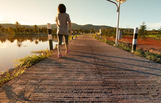 Mulher asiática jovem fitness está andando depois correu no parque tropical
