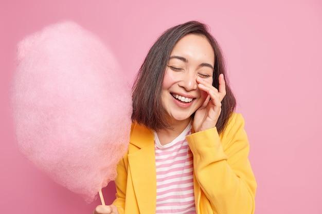 Mulher asiática jovem morena cheia de alegria fecha os olhos, sorri e se diverte alegremente enquanto caminha na rua durante o dia de verão segurando um delicioso algodão doce isolado sobre a parede rosa recebe uma guloseima