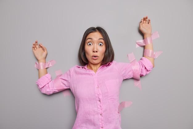 Mulher asiática jovem morena estupefata encara os olhos esbugalhados com medo de algo terrível usa camisa pik posa contra parede cinza pega por alguém