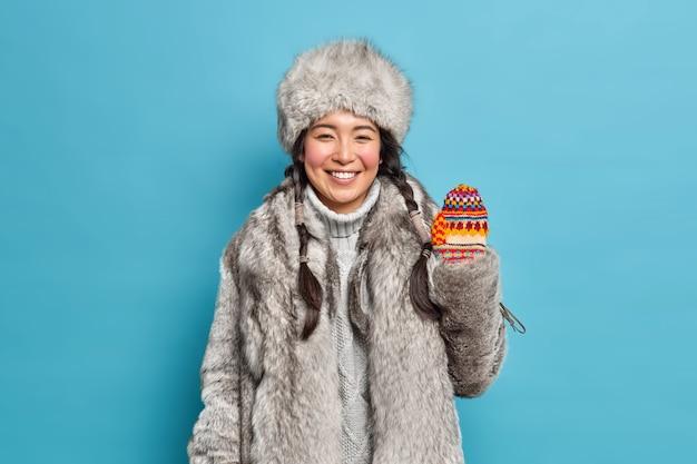Mulher asiática jovem morena positiva usa casaco de pele e chapéu acena com a mão em luvas de malha sorrisos alegremente curtindo as férias de inverno ou feriados isolados sobre a parede azul