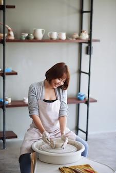 Mulher asiática jovem muito positiva usando costela de madeira rígida para alcançar a melhor forma de prato em oleiro.