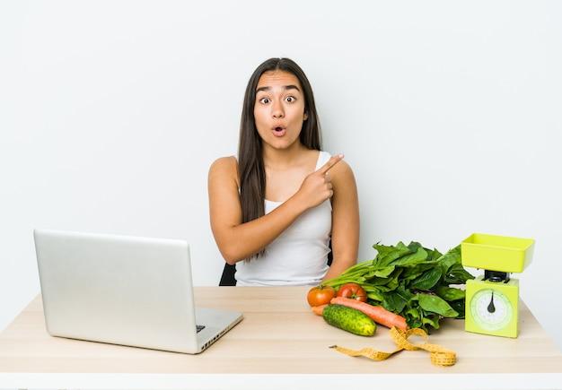 Mulher asiática jovem nutricionista isolada na parede branca, apontando para o lado.
