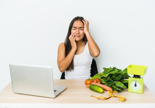 Mulher asiática jovem nutricionista isolada na parede branca, chorando e chorando desconsoladamente.