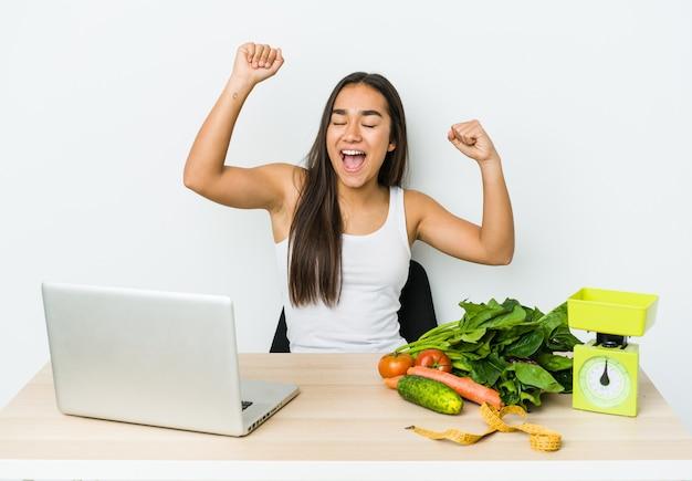 Mulher asiática jovem nutricionista isolada na parede branca comemorando um dia especial, pula e levanta os braços com energia.
