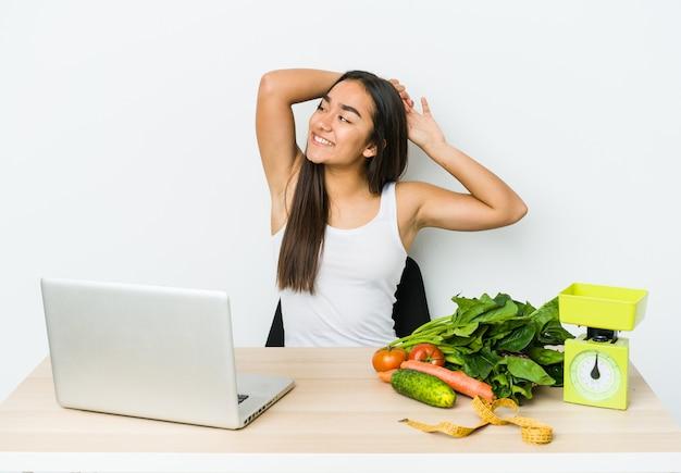Mulher asiática jovem nutricionista isolada na parede branca, esticando os braços, posição relaxada.