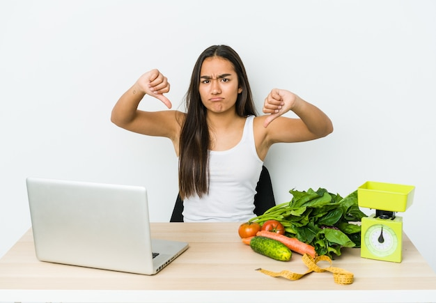 Mulher asiática jovem nutricionista isolada na parede branca, mostrando o polegar para baixo e expressando antipatia.