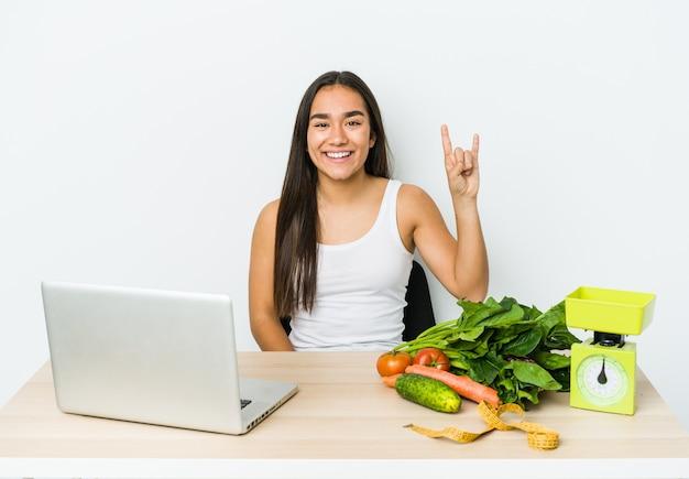 Mulher asiática jovem nutricionista isolada na parede branca, mostrando um gesto de chifres como um conceito de revolução.