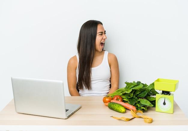 Mulher asiática jovem nutricionista isolada na parede branca mulher asiática jovem traumatologista isolada na parede branca gritando por um espaço de cópia