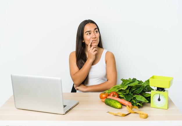 Mulher asiática jovem nutricionista isolada na parede branca, olhando de soslaio com expressão duvidosa e cética.