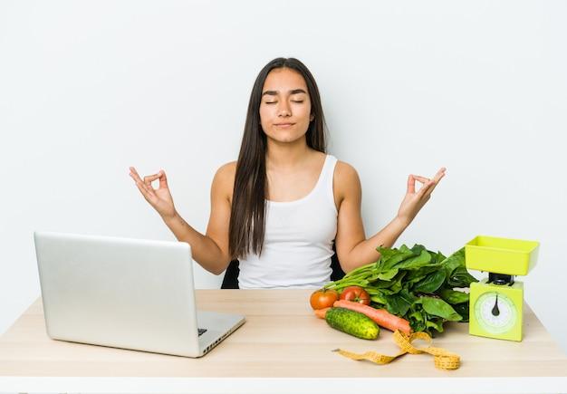 Mulher asiática jovem nutricionista isolada na parede branca relaxa após um árduo dia de trabalho, ela está realizando ioga.