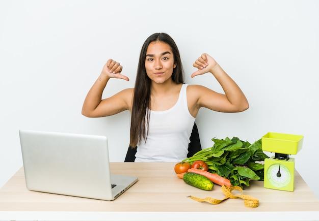 Mulher asiática jovem nutricionista isolada na parede branca sente-se orgulhosa e autoconfiante, exemplo a seguir.