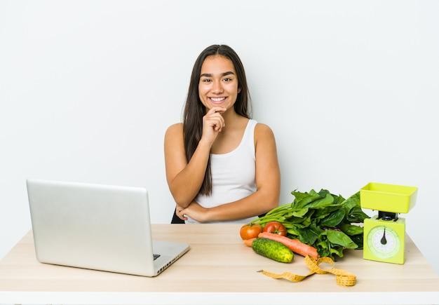 Mulher asiática jovem nutricionista isolada na parede branca, sorrindo feliz e confiante, tocando o queixo com a mão.
