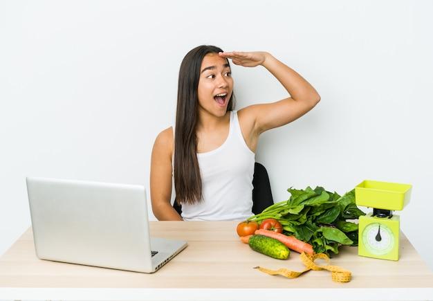 Mulher asiática jovem nutricionista isolada no branco, olhando para longe, mantendo a mão na testa.