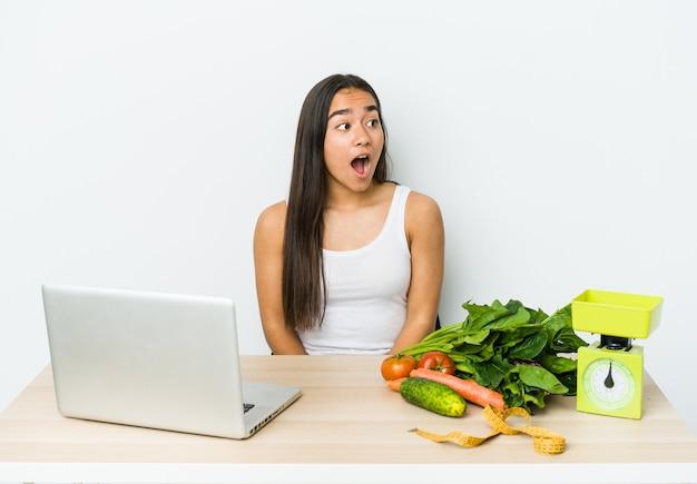 Mulher asiática jovem nutricionista isolada no fundo branco, sendo chocada por causa de algo que ela viu.