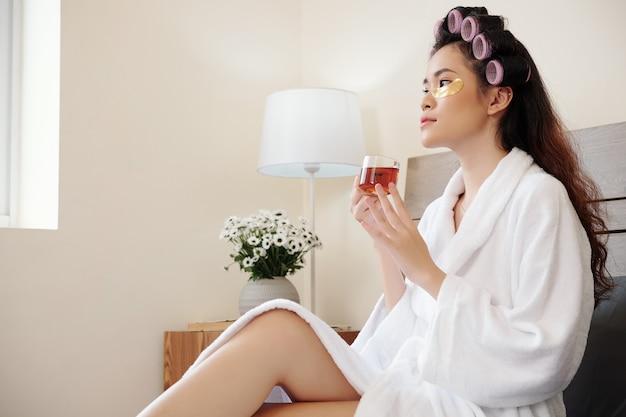 Mulher asiática jovem pensativa com uma xícara de chá, sentada na cama com adesivos sob os olhos, bebendo chá e relaxando após o banho