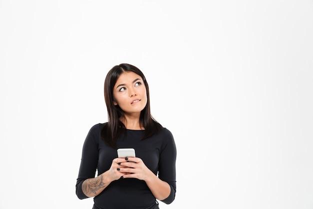 Mulher asiática jovem pensativa conversando pelo telefone móvel
