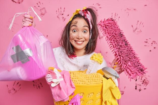 Mulher asiática jovem positiva pega lixo em saco de polietileno segura o esfregão sujo se preocupa com a pureza e tem o rosto sujo ocupado lavando roupa isolado na parede rosa