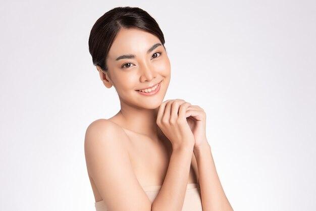 Mulher asiática jovem sorridente bonita com maquiagem natural de pele limpa e dentes brancos