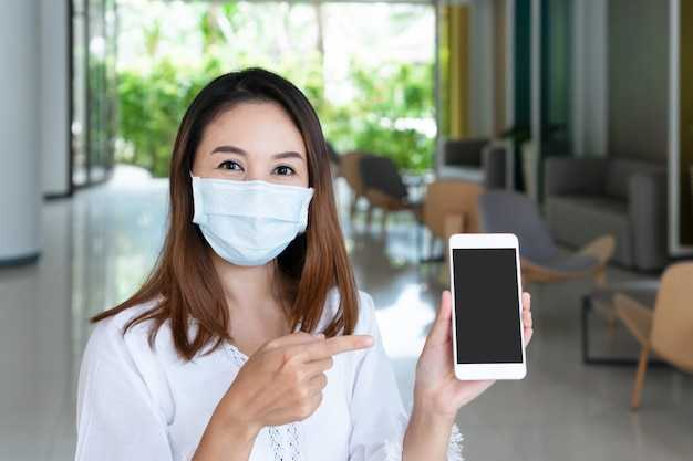 Mulher asiática jovem sorridente com máscara facial protetora segurando o smartphone para o espaço da cópia.
