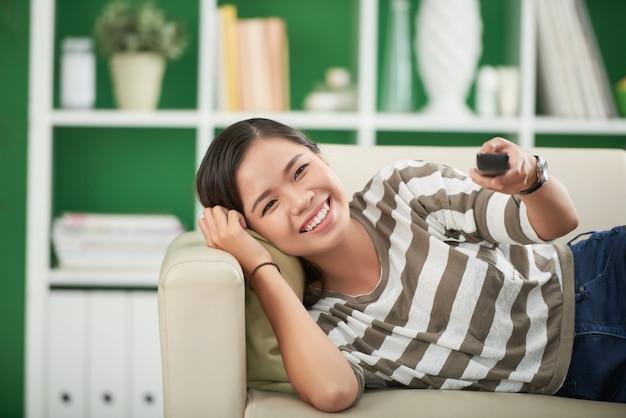 Mulher asiática jovem sorridente, deitado no sofá em casa, olhando em linha reta e pressionando o controle remoto