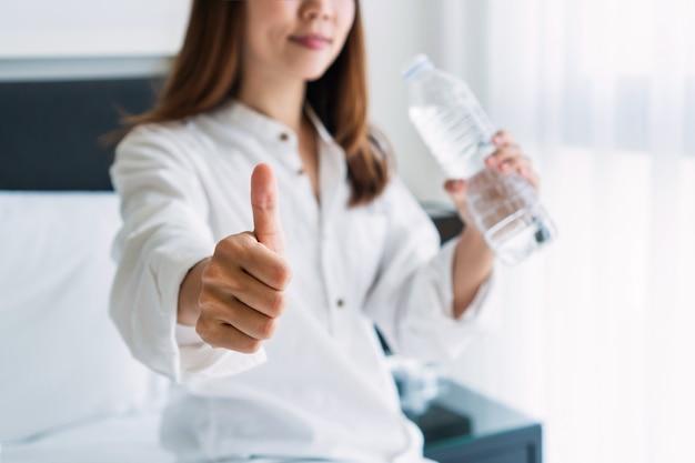 Mulher asiática jovem sorridente feliz bebendo água depois de acordar de manhã.