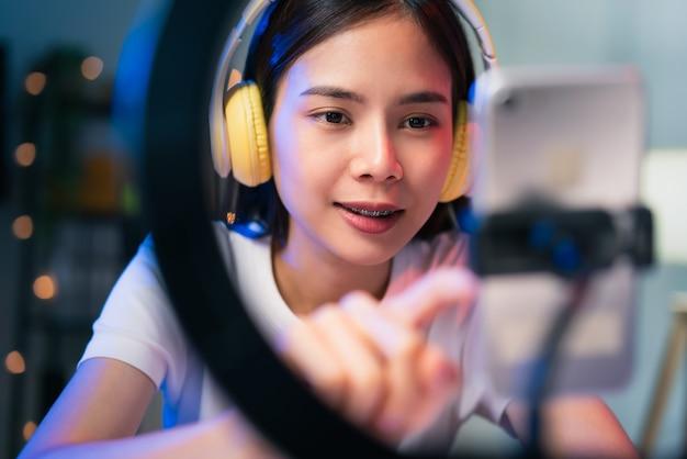 Mulher asiática jovem sorridente usando fone de ouvido e transmissão ao vivo na internet e lendo comentários com pessoas nas redes sociais no smartphone.