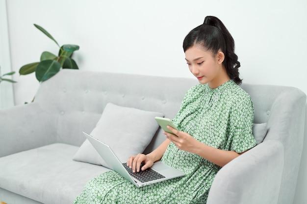 Mulher asiática jovem sorridente usando um telefone celular enquanto está sentada em um sofá em casa com um laptop