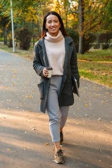 Mulher asiática jovem sorridente, vestindo um casaco, caminhando ao ar livre no parque, ouvindo música com fones de ouvido, segurando uma xícara de café para viagem