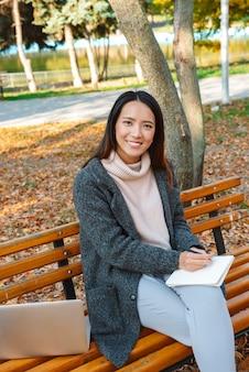 Mulher asiática jovem sorridente, vestindo um casaco, sentada em um banco do parque, trabalhando em um computador laptop, fazendo anotações