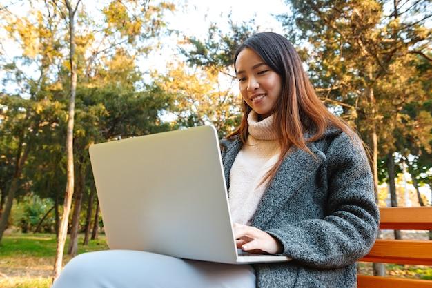 Mulher asiática jovem sorridente, vestindo um casaco, sentada em um banco do parque, trabalhando em um computador laptop