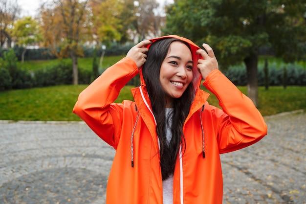 Mulher asiática jovem sorridente, vestindo uma capa de chuva, caminhando ao ar livre na chuva, posando com um capuz