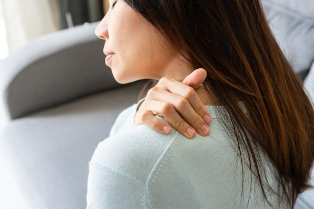 Mulher asiática jovem temperamental sente dor no pescoço enquanto está sentada no sofá da sala de estar. conceito de problema de saúde. fechar-se