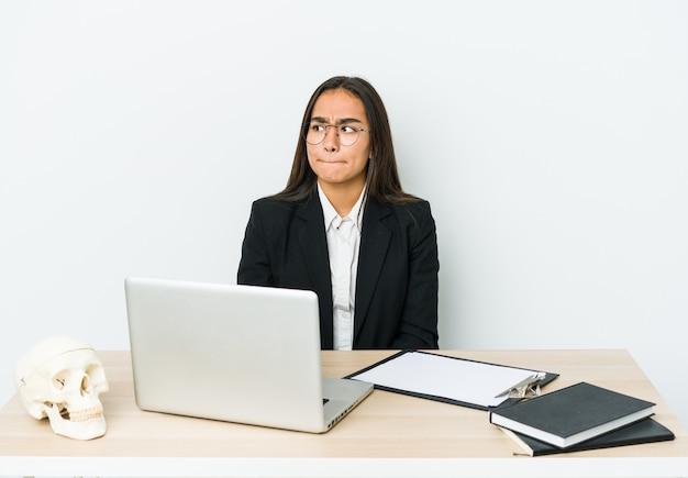 Mulher asiática jovem traumatologista isolada na parede branca confusa, sente-se em dúvida e insegura.