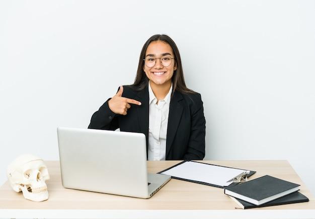 Mulher asiática jovem traumatologista isolada na parede branca pessoa apontando com a mão para um espaço da cópia da camisa, orgulhosa e confiante