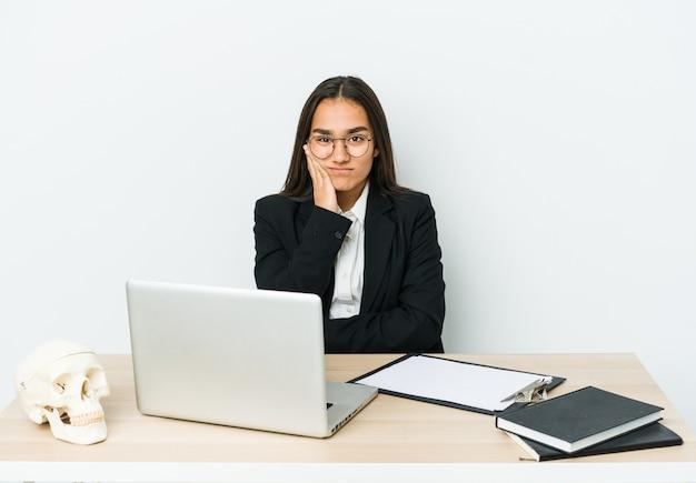 Mulher asiática jovem traumatologista isolada na parede branca que está entediada, cansada e precisa de um dia de relaxamento.