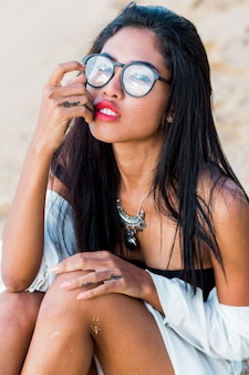 Mulher asiática l posando em uma praia tropical à noite. corpo bronzeado perfeito. jóias, pulseira e colar.