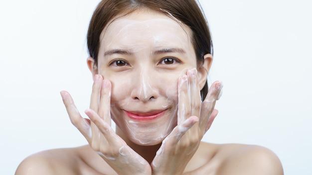 Mulher asiática lava o rosto com espuma de limpeza de bolha isolada