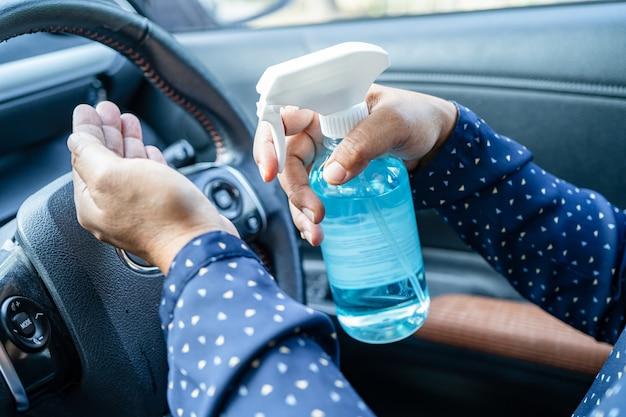 Mulher asiática lavando as mãos com álcool gel desinfetante azul para proteger o coronavírus no carro