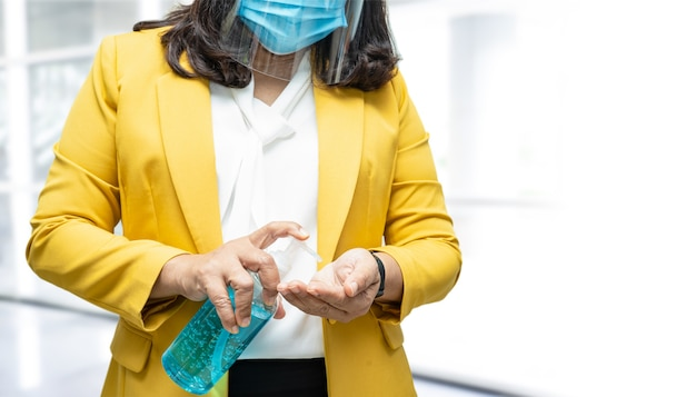 Mulher asiática lavando as mãos com álcool gel desinfetante azul